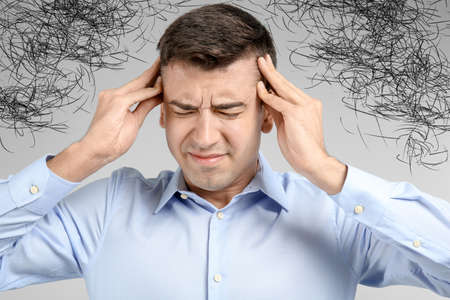 Stressed man with mess in his head on light background