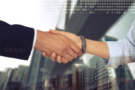 Multiple exposure of partners shaking hands, coins and city. Business values