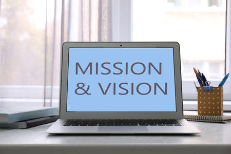 Modern laptop with phrase MISSION AND VISION on screen indoors