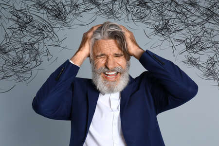 Stressed man with mess in his head on grey background