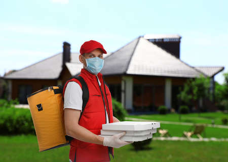 Courier in protective mask and gloves with order outdoors. Delivery service during coronavirus quarantine Banque d'images