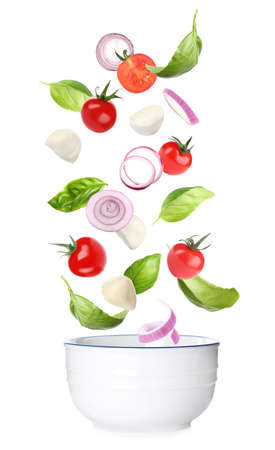Mozzarella cheese, tomatoes, onion and basil leaves falling into bowl on white background