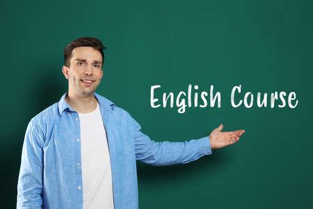 Portrait of young English teacher near green chalkboard