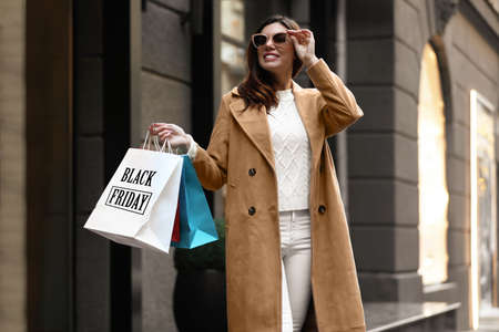 Young woman holding shopping bags on city street. Black Friday Sale