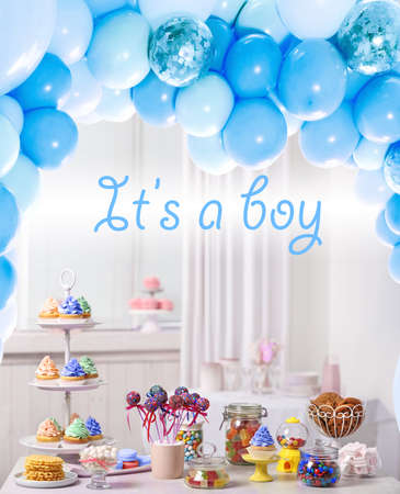 Baby shower party for boy. Tasty treats on table in room decorated with balloons