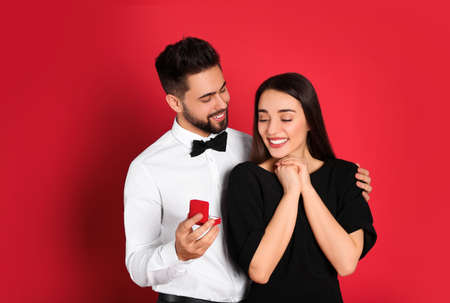 Man with engagement ring making marriage proposal to girlfriend on red background