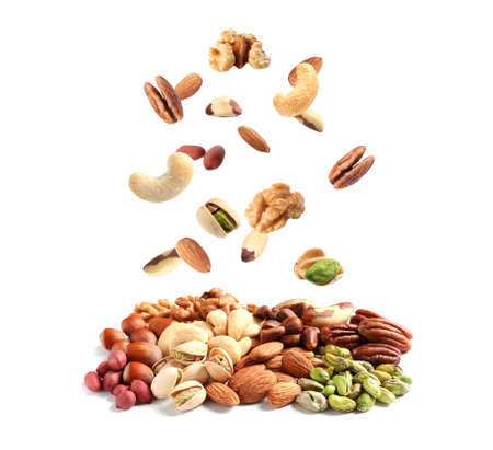 Different nuts falling into pile on white background Stock Photo