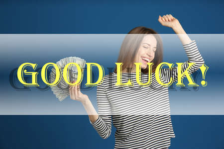 Happy young woman with cash money on blue background. Good luck Banque d'images