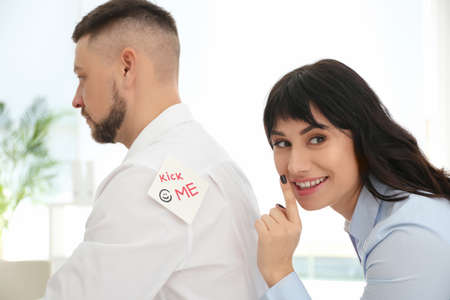 Young woman sticking KICK ME note to colleague's back in office. April fool's day Stockfoto