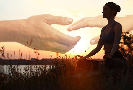 Double exposure of woman meditating and hands reaching each other outdoors at sunset. Yoga helping in daily life: harmony of mind, body, and soul Banco de Imagens