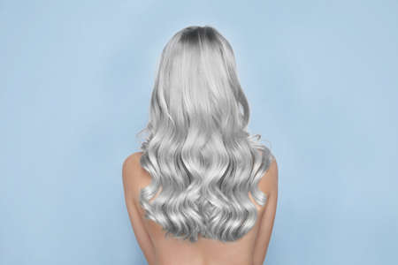 Woman with gray hair on light background, back view