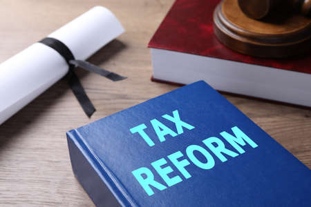 Book with words TAX REFORM on wooden table, closeup