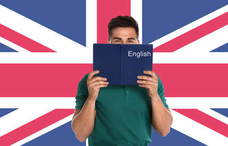 Handsome young man reading book and flag of Great Britain on wall. Learning English