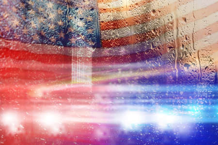Double exposure of American flag and police cars on street at night