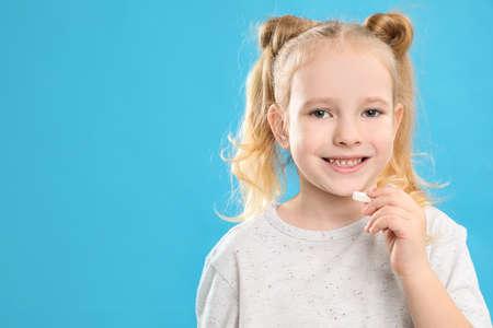 Little girl taking vitamin pill on light blue background. Space for text