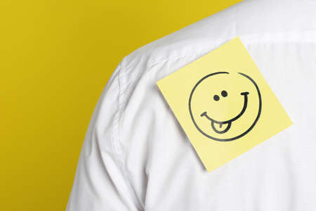 Man with funny face sticker on back against yellow background, closeup. April fool's day