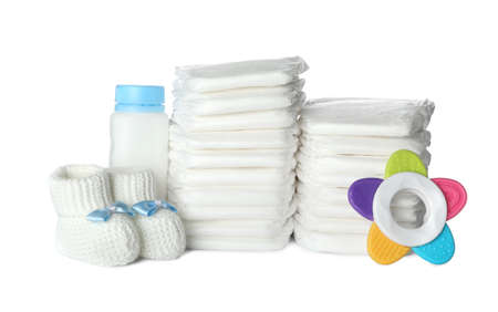 Disposable diapers, child's booties, teether and bottle on white background Banque d'images