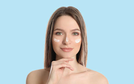 Young woman with sun protection cream on face against light blue background 스톡 콘텐츠