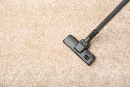 Entfernen von Schmutz vom Teppich mit einem modernen Staubsauger im Innenbereich, Ansicht von oben. Platz für Text