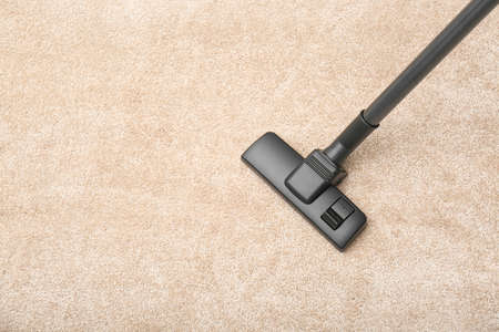 Removing dirt from carpet with modern vacuum cleaner indoors, top view. Space for text