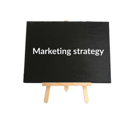 Blackboard with phrase MARKETING STRATEGY on wooden easel against white background Stock Photo