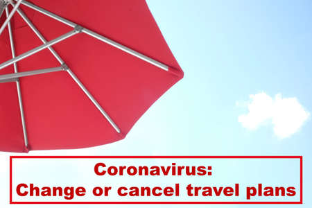Vacation cancellation concept. View of red umbrella and blue sky on sunny day