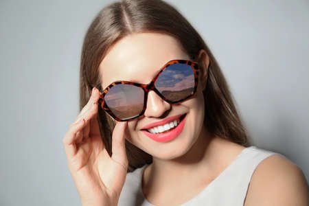 Young woman wearing stylish sunglasses with reflection of sky on light grey background