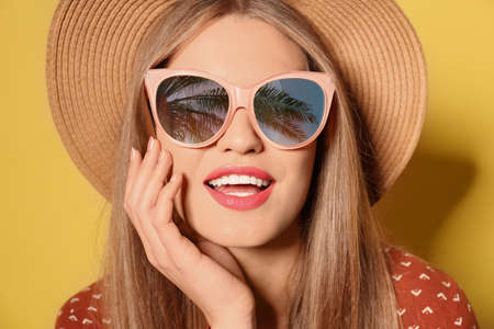 Young woman wearing stylish sunglasses with reflection of palm trees and hat on yellow background 스톡 콘텐츠 - 146386635