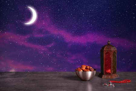 Traditional Ramadan lantern, dates and prayer beads on table. Muslim holiday
