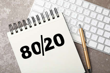 Pareto principle concept. Notebook with 80/20 rule representation, pen and keyboard on grey background, flat lay