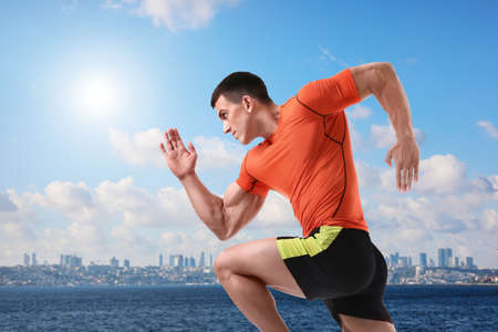 Athletic young man running near sea on sunny day