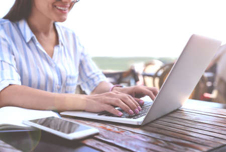 Woman working with laptop at outdoor cafe on sunny day, closeup Banco de Imagens - 150647689