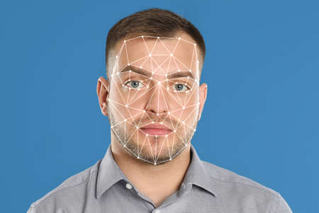 Facial recognition system. Young man with biometric identification scanning grid on light blue background