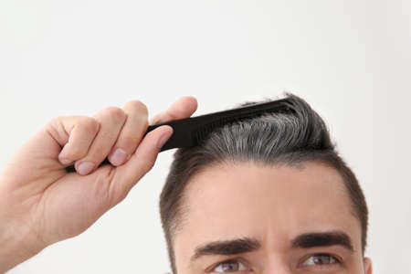 Young man with grey hair on white background, closeup