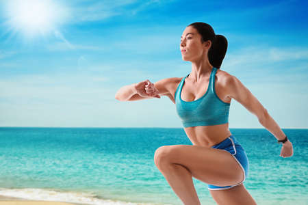 Athletic young woman running near sea on sunny day, space for text