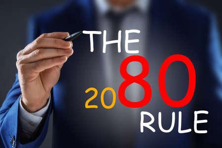 Pareto principle concept. Man writing 80/20 rule, closeup