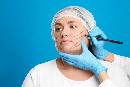 Doctor drawing marks on woman's face for cosmetic surgery operation against blue background. Double chin problem
