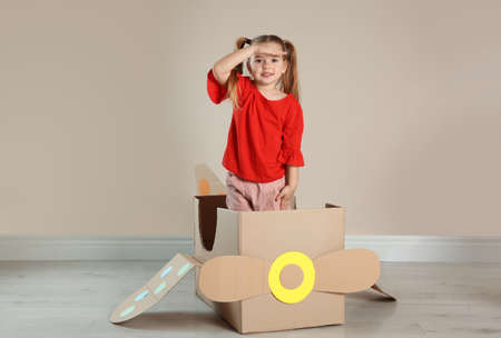 Cute little child playing with cardboard plane near beige wall