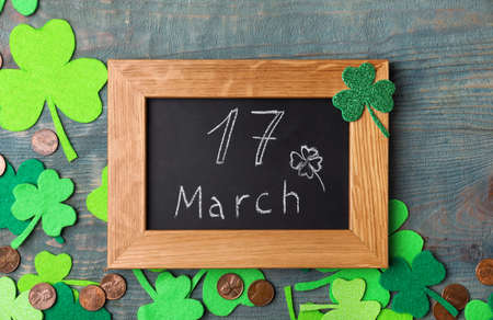 Chalkboard with written 17 March, clover leaves and gold coins on blue wooden background. St. Patrick's Day celebration