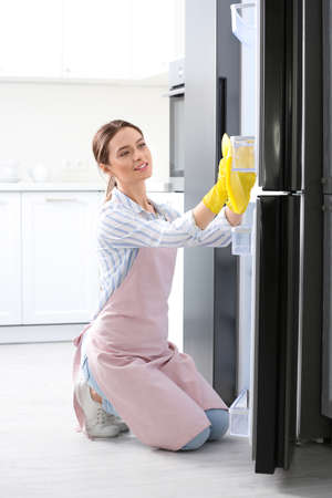Woman in rubber gloves cleaning refrigerator at home