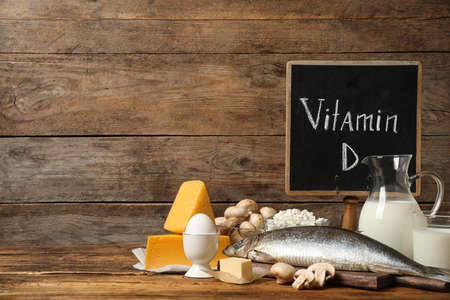 Chalkboard with phrase VITAMIN D and fresh products on wooden table Zdjęcie Seryjne