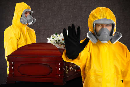 Funeral during coronavirus pandemic. People in protective suits near casket indoors