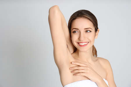 Young woman showing armpit with smooth clean skin on light grey background