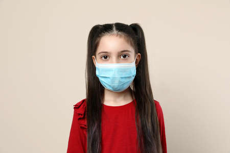 Little girl in medical mask on beige background. Virus protection