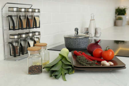 Fresh vegetables on white countertop in kitchen Stock Photo