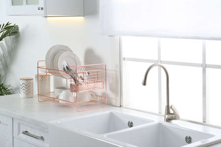 Clean dishes on drying rack in modern kitchen interior Stockfoto