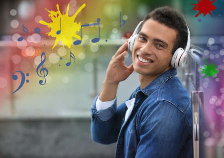 Young African-American man with headphones listening music outdoors Banco de Imagens