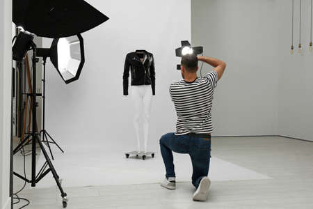 Professional photographer taking picture of ghost mannequin with stylish clothes in modern photo