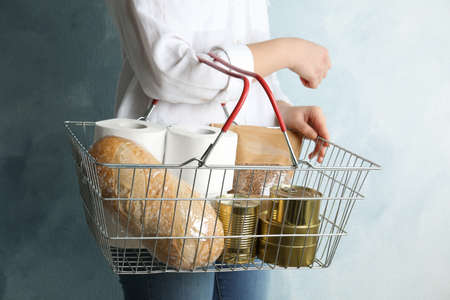 Woman holding shopping basket with products and toilet paper rolls on light blue background, closeup. Panic caused by virus