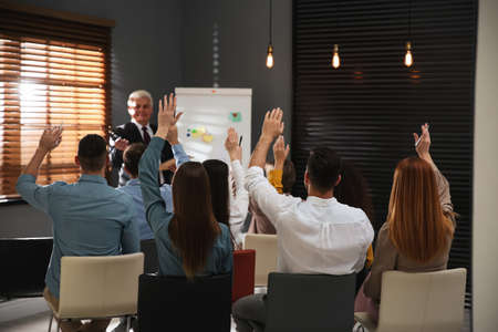 People raising hands to ask questions at seminar in office